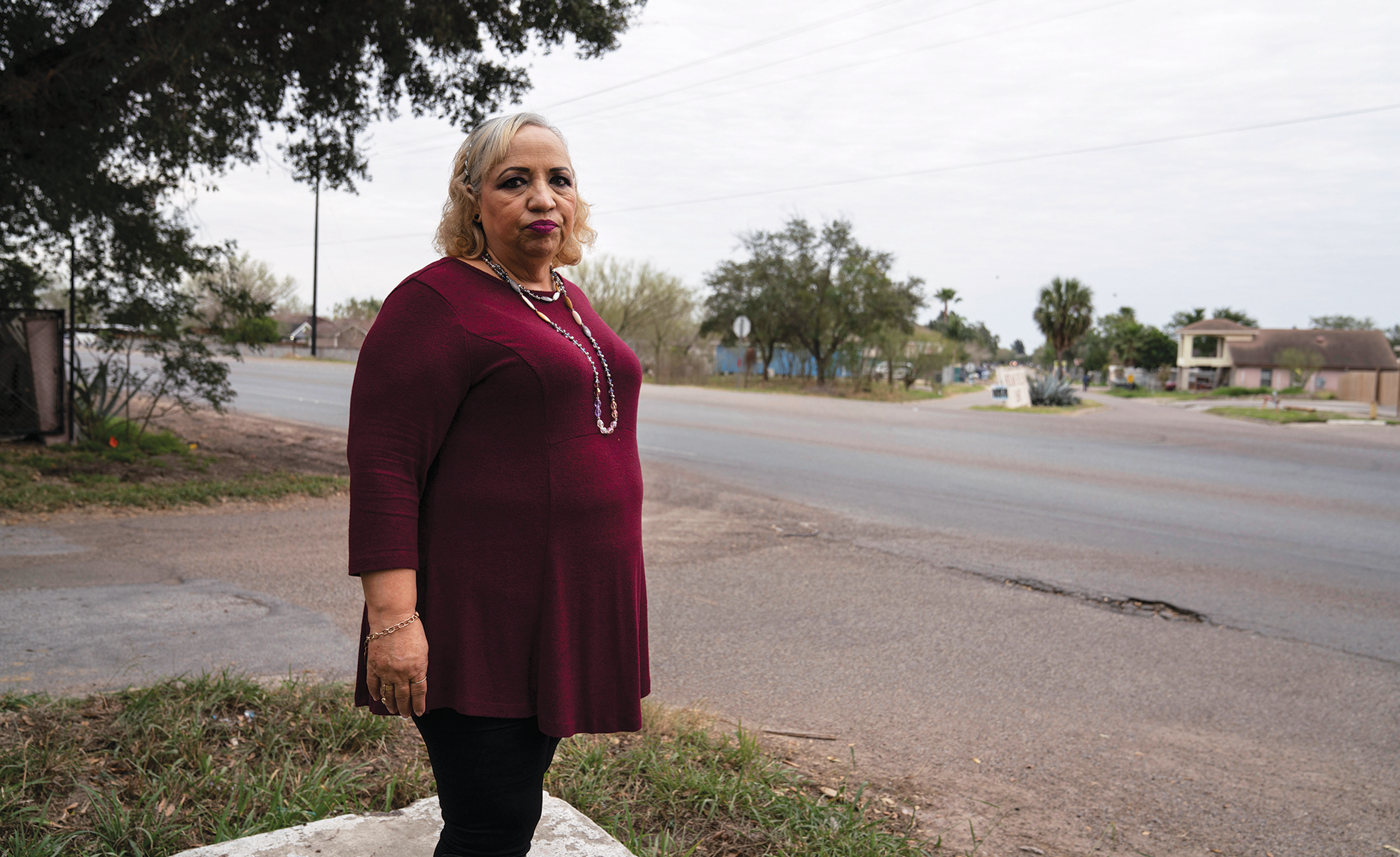 Lourdes Salinas stands in the elevated spot where she made phone calls and helped to evacuate residents during the June 2018 flood.