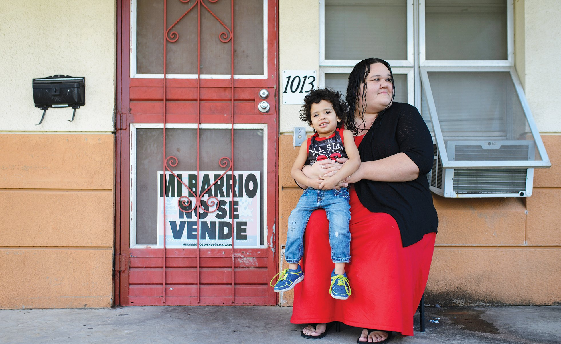 Kayla Miranda, who has lived at Alazán-Apache Courts since 2017, waits with her nephew De'Andre for her kids to get home from school.