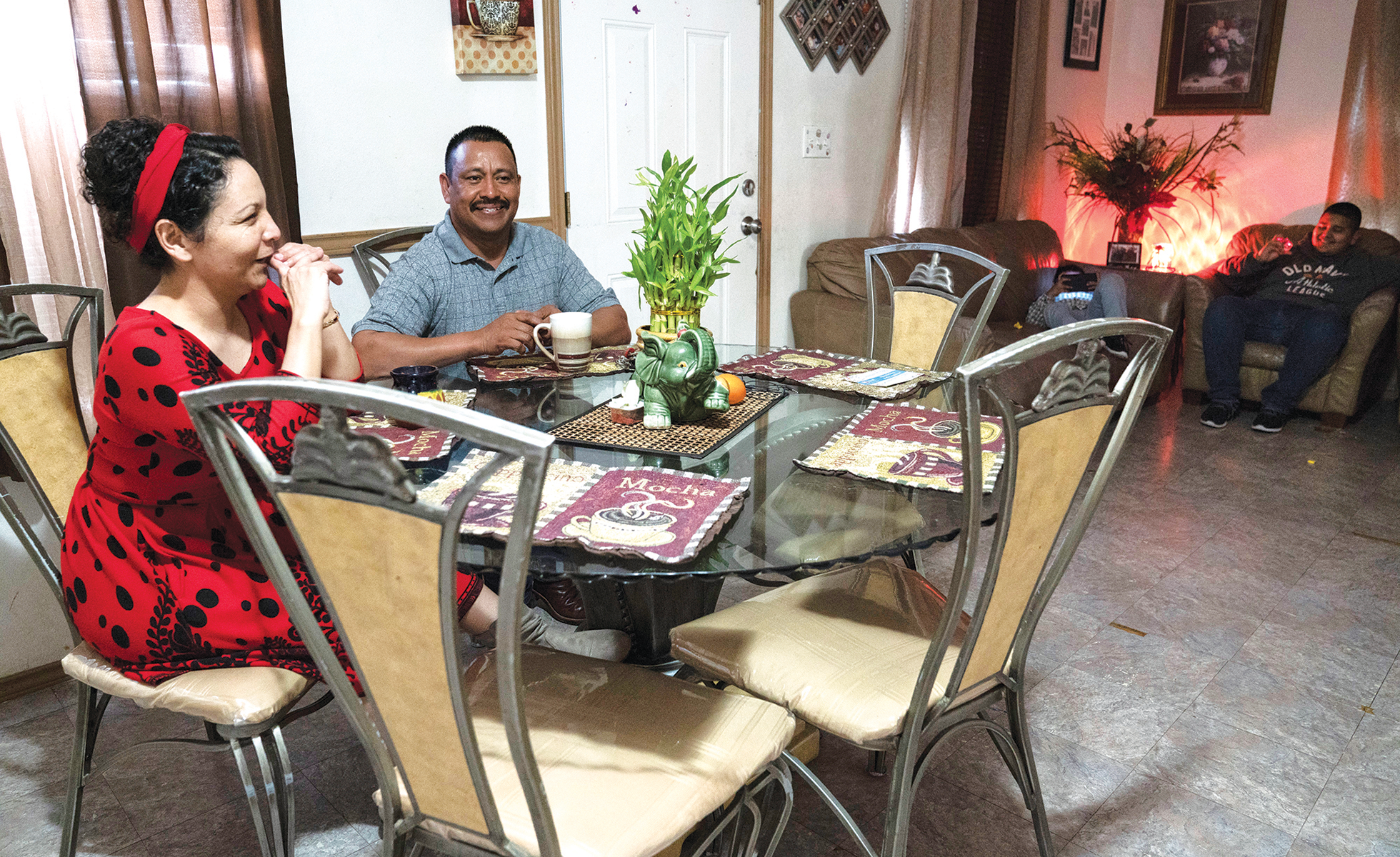 Capetillo and her husband sit at their kitchen table in the home they share with their four kids.