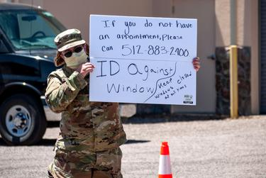 A member of the National Guard holds up a sign at a drive-thru testing center in Alpine.