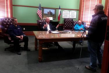 Anna Howard, left, director of Associated Ambulance Authority; county Judge John Howard; and Sheriff Butch Blackburn appear at a press conference with Roger Estlack, who runs the local newspaper.