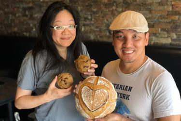 Debbie Chen, co-owner of Houston's Shabu House, and Nguyen T. Nguyen, a local artist and photographer, hold sourdough bread and cookies. Chen is helping organize an effort to use donations to feed front-line workers during the pandemic.