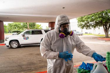 Chris Luna, a worker for Code 4 Event Management, puts on personal protective equipment as he prepares to disinfect a building during the COVID-19 pandemic in Austin on Wednesday.