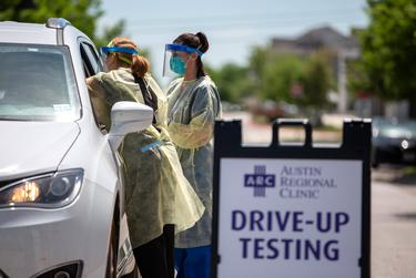 Nurse Kristen Howell, left, and medical lab technician Amanda Hernandez administer a test for the new coronavirus at the Austin Regional Clinic drive-thru testing site in Kyle.