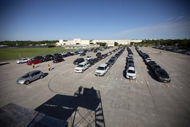 Cars lined up Wednesday at LBJ Early College High School in Austin to receive food and hygiene products from the Central Texas Food Bank.