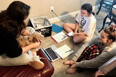 Jillian Gilmore, left, and Allyson Dymond, right, help Genevieve Gilmore with her homework.