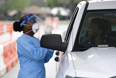 Harris County Health Department nurse Harriet Lewis administers a coronavirus test at Stallworth Stadium in Baytown on March 21, 2020.