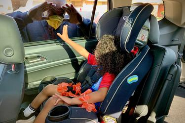 Jerry Norman greets his 3-year-old grandson, Joseph Lee, through an SUV window in Midland.