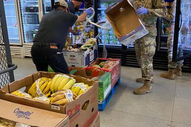 Texas Army National Guard soldiers have been among the volunteers at the Dallas food pantry where Liz Salas works. Food donations, including fresh fruit, have been increasing lately.