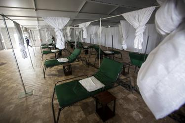 Cots are spread out along a tiled floor in one of the medical tents at NRG Park in Houston.