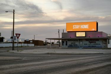 The intersection of Kermit Highway and Andrews Highway in Odessa is empty as an advertisement urges people to stay home during the coronavirus pandemic.