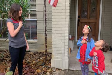 Lea Shah and her children, Nina and Nikhil, recite the Pledge of Allegiance outside their San Antonio home.