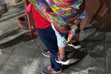 A migrant from Guatemala who is waiting in Ciudad Juárez to claim U.S. asylum carries her child on her back.