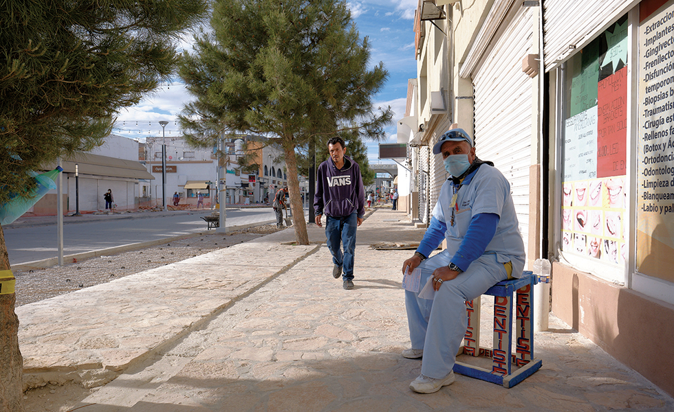 A dentist sits outside of his practice in central Juárez. Although medical facilities have not been ordered to close, they've taken a hit, as they rely heavily on uninsured American customers.
