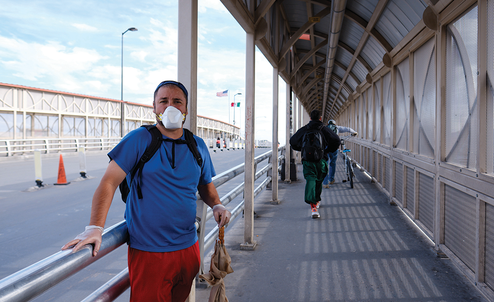 A man asking for money on the U.S. side of the Paso del Norte International Bridge protects himself with a mask and latex gloves.
