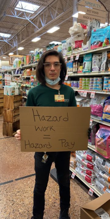 """Joshua Cano holds protest sign reading """"Hazard Work = Hazard Pay"""" in a Sprouts grocery store in McAllen."""