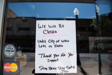 A hand-written signs alerts costumers that Jake's Texas Tea House in Waco is closed indefinitely.